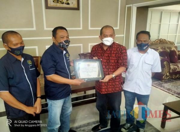 Ketua PWI Malang Raya, Cahyono (dua dari kiri) saat memberikan cinderamata pada Ketua DPRD Kota Malang, I Made Rian Diana Kartika (Anggara Sudiongko/MalangTIMES)