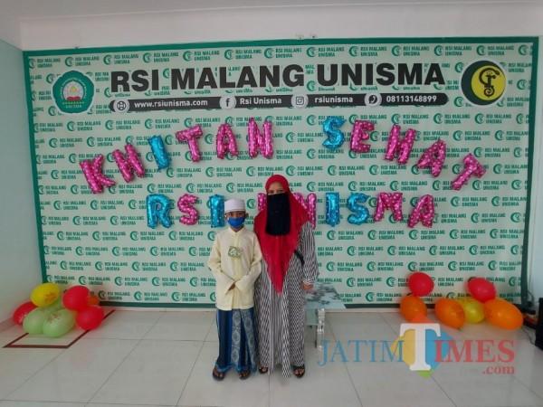 Salah satu peserta program khitan masal RSI Unisma bernama Fiyan dan orang tua yang mendampingi, Sabtu (27/2/2021). (Foto: Tubagus Achmad/MalangTIMES)