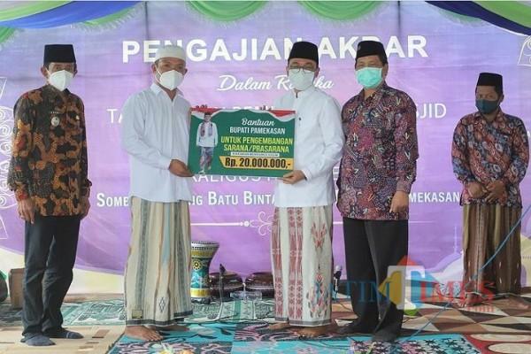 Bupati Pamekasan Baddrut Tamam saat menyerahkan bantuan secara simbolis kepada perwakilan pengurus Masjid Darul Karomah (Foto: Istimewa)