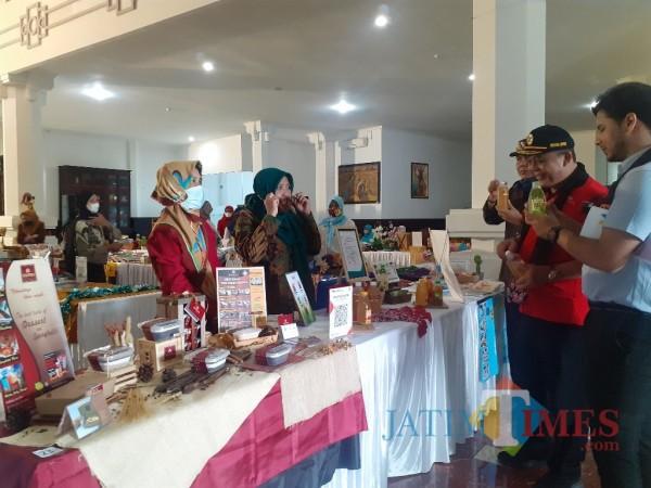 Ketua DPRD Kota Malang I Made Riandana Kartika (bertopi) saat meninjau pameran UMKM di Hall Gedung DPRD Kota Malang. (Arifina Cahyanti Firdausi/MalangTIMES).
