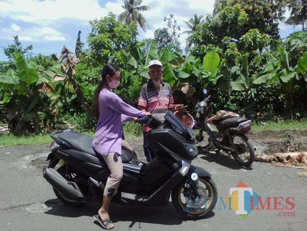 Asmuni (80 tahun) sukarela menjadi tenaga penarik sumbangan sukarela untuk perbaikan jalan (Nurhadi/JatimTimes)