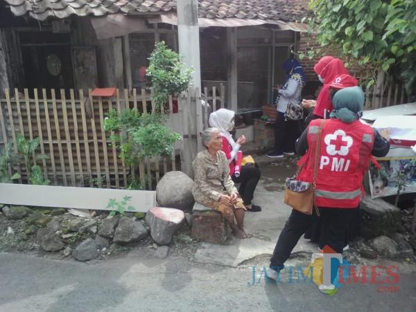 Bu Amenah bersama relawan Sibat kelurahan Mojopanggung di depan rumahnya yang direnovasi Nurhadi Banyuwangi Jatim Times