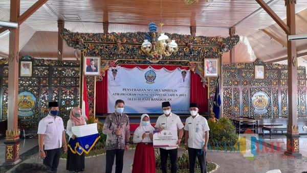 Bupati Bangkalan R Abdul Latif Amin Imron didampingi oleh Kadisdik saat menyerahkan bantuan ATM PIP (Foto: Imam JatimTIMES)