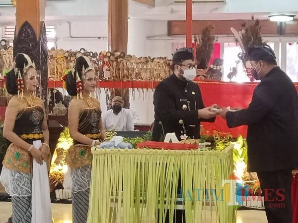 Bupati Kediri Hanindhito Himawan Pramana ketika menyerahkan potongan tumpeng kepada Ketua DPRD Kabupaten Kediri Dodi Purwanto. (Foto: Bams Setioko/JatimTIMES)