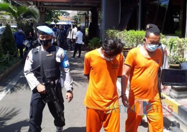 Kedua pelaku pembunuhan pemandu lagu di Kabupaten Malang saat digelandang anggota Polres Malang (foto: Hendra Saputra/MalangTIMES)