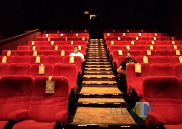 Manajer Cinema XXI Sutardi saat mengecek kondisi kursi duduk gedung bioskop.(Eko arif s/Jatimtimes)