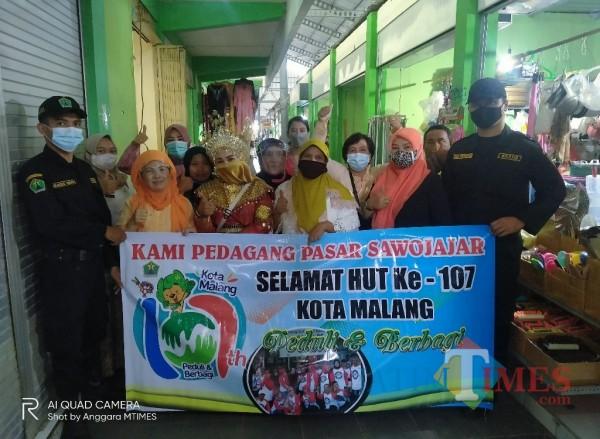 Para pedagang Pasar Sawojajar yang berfoto bersama dengan mengenakan pakaian adat daerah (Anggara Sudiongko/ MalangTIMES)