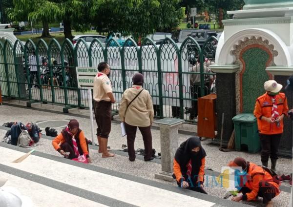 Anggota Kwarcab Pramuka Kota Malang saat bersih-bersih di Masjid Jami' (foto: Hendra Saputra/MalangTIMES)