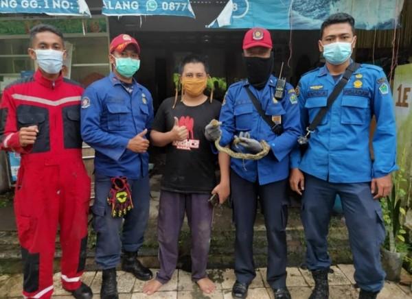 Petugas UPT Pemadam Kebakaran Kota Malang usai melakukan penyelamatan hewan yakni ular, Selasa (16/3/2021). (Foto: UPT Pemadam Kebakaran Kota Malang)