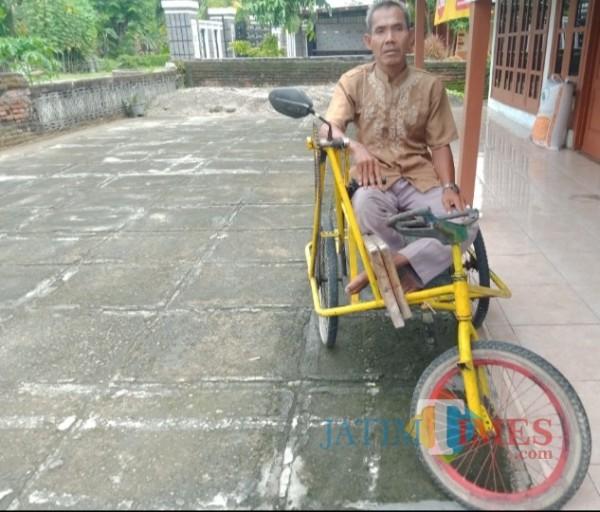 Sunarto di atas sepeda roda tiga yang sangat membantu untuk transportasi memasarkan keset hasil karyanya