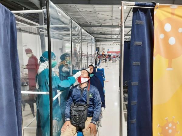 Petugas kesehatan yang sedang melakukan tes rapid antigen kepada calon penumpang kereta api. (Foto: Humas PT KAI Daop 8 Surabaya)