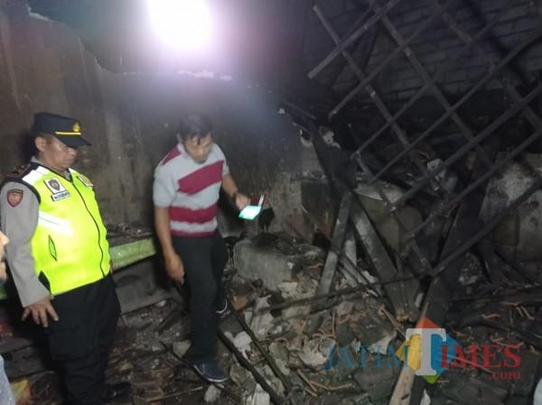 Kapolsek Sumbermanjing Wetan, Iptu Mashudianto (kiri) saat meninjau rumah terdampak gempa (foto:Hendra Saputra/MalangTIMES)