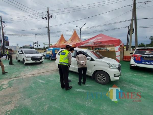 Petugas dari Satlantas Polres Malang saat melakukan pemeriksaan terhadap penumpang dari luar wilayah Malang. (Foto: Tubagus Achmad/ JatimTIMES)