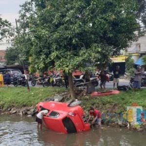 Mobil Ayla Terjun ke Sungai Usai Tabrak Lapak Pedagang Buah di Jombang