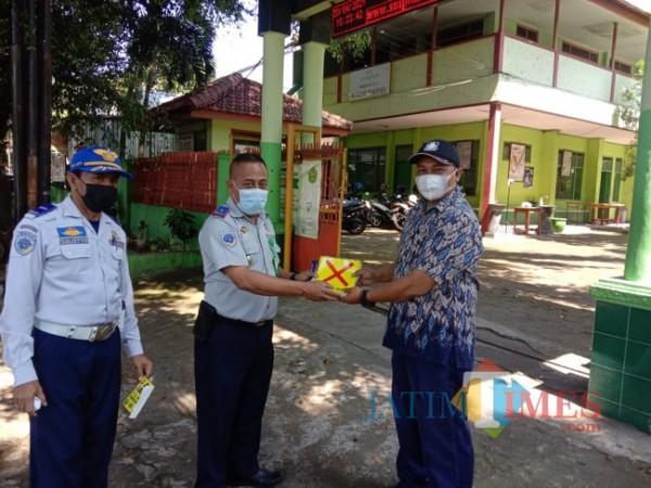 Petugas Dishub Kota Malang saat membagikan stiker protokol kesehatan pencegahan Covid-19 di salah satu sekolah di Kota Malang. (Foto: Istimewa).