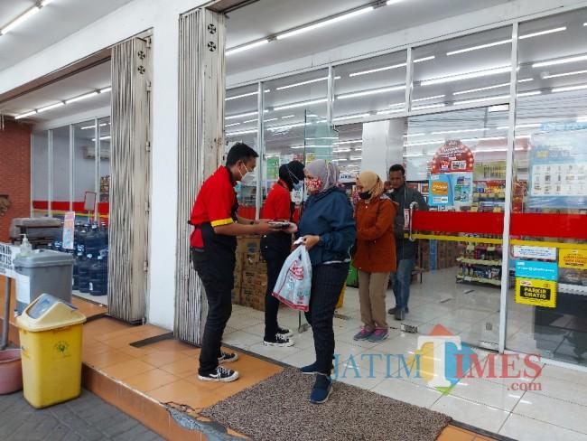 Pegawai Alfamart saat membagikan takjil nasi kotak kepada pengunjung.