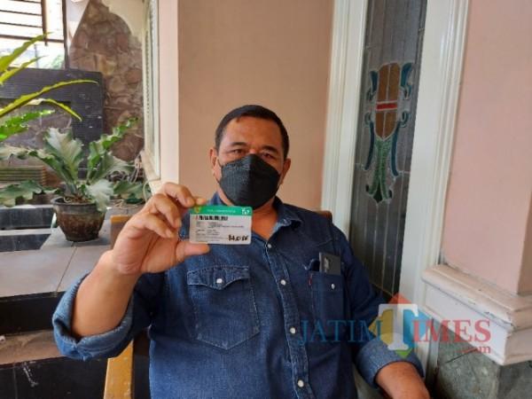 M. Zuhdy Achmadi atau yang akrab disapa Didik saat menunjukkan KIS (Kartu Indonesia Sehat), Sabtu (24/4/2021). (Foto: Tubagus Achmad/MalangTIMES)