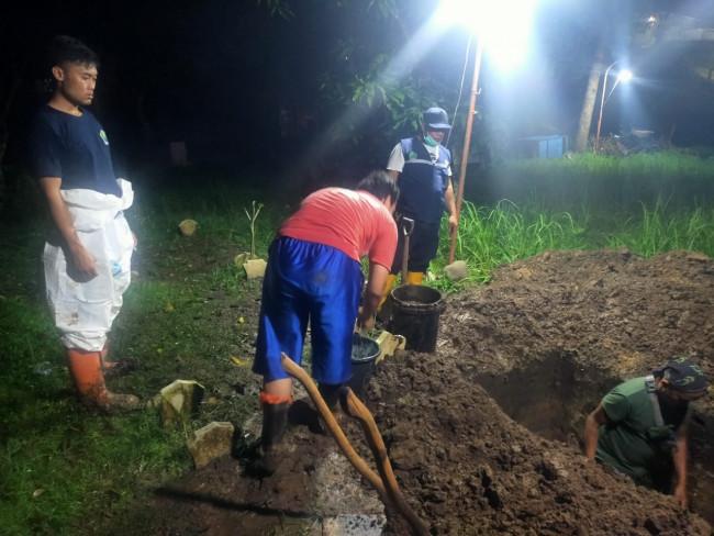 Petugas pemakaman UPT PPU DLH Kota Malang yang tengah melakukan pemakaman hingga malam hari (Ist)