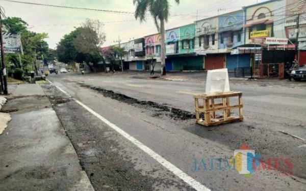 Jalan sekitar pasar yang rusak akibat air limbah yang dibuang pedagang. (Dok MalangTIMES)