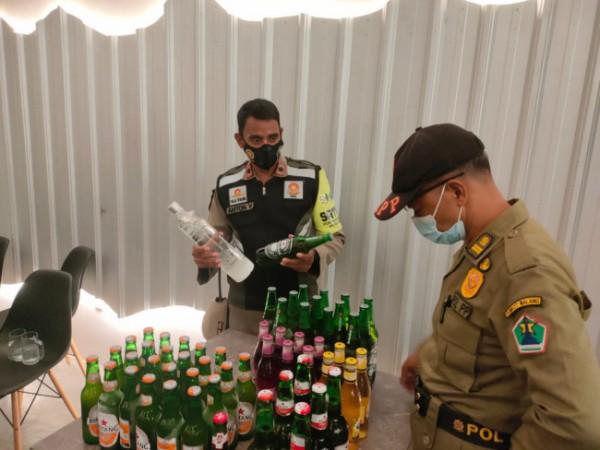 Petugas Satpol PP Kota Malang saat melakukan pengamanan terhadap ratusan botol minuman keras di Kafe Ko.boy, Kota Malang, Sabtu (1/5/2021) malam. (Foto: Satpol PP Kota Malang)