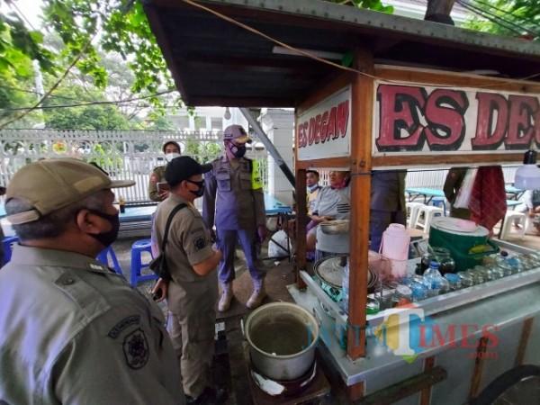 Petugas Satpol PP Kota Malang saat memberikan peringatan terakhir kepada pedagang yang berada di seberang Mal Alun-Alun Kota Malang, Minggu (2/5/2021). (Foto: Tubagus Achmad/MalangTIMES)