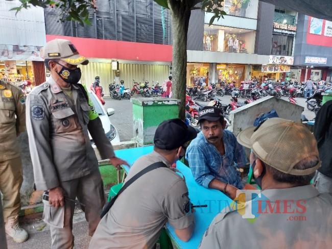 Petugas Satpol PP Kota Malang sedang melakukan negosiasi dan sosialisasi kepada PKL di Jalan Agus Salim.