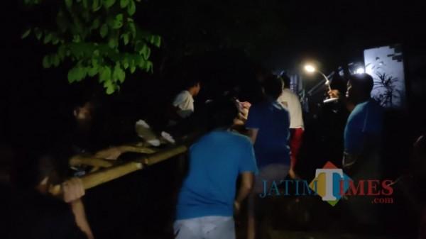warga saat mengevakuasi korban menggunakan tandu darurat yang terbuat dari tangga (foto : istimewa / Jatim TIMES)