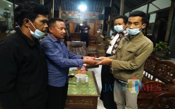 Ketua panitia saat mengembalikan uang pada Fajar Dwi Nugroho calon Perangkat Desa Gondanggunung /  Foto : Anang Basso / Tulungagung TIMES