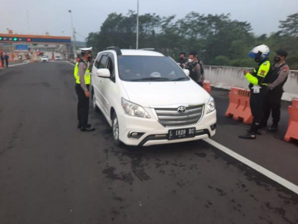 Petugas Satlantas Polresta Malang Kota saat melakukan pengecekan kelengkapan dokumen kendaraan luar kota yang keluar dari exit tol Madyopuro, Kota Malang. (Foto: Satlantas Polresta Malang Kota)