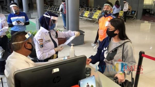 Petugas di salah satu stasiun yang memeriksa kelengkapan dokumen keberangkatan calon penumpang. (Foto: Humas PT KAI Daop 8 Surabaya for JatimTIMES)