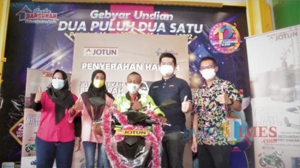 Stevan Suryanto selaku Decorative Retail Consultant PT Jotun Indonesia didampingi Direktur Graha Bangunan Daniel Lim menyerahkan hadiah sepeda motor kepada customer.(Foto : Aunur Rofiq/BlitarTIMES)