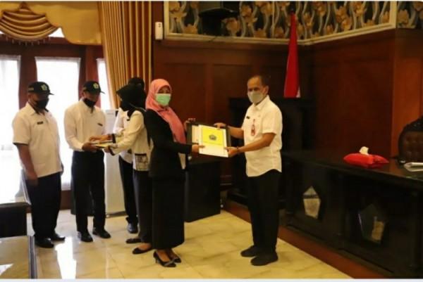 Kepala DLH Kota Malang, Wahyu Setianto saat menyerahkan penghargaan Adiwiyata di Ruang Sidang Balai Kota Malang, Rabu (5/5/2021) kemarin. (Foto: istimewa)
