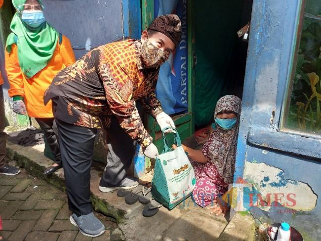 Kepala Kantor Kemenag Kota Malang Muhtar Hazawawi saat memberikan paket sembako kepada warga di Kampung Qoriyah Sakinah.