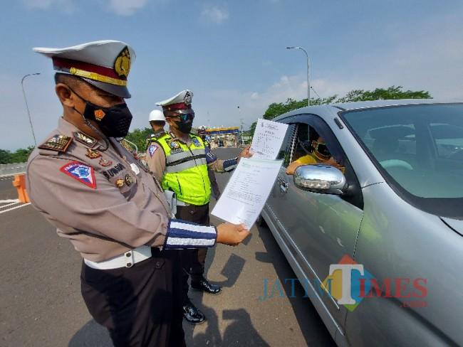 Petugas Pos Pengamanan Exit Tol Madyopuro Malang saat memeriksa kelengkapan dokumen perjalanan.