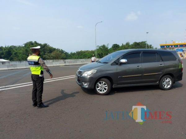 Petugas pos pengamanan Exit Tol Madyopuro Malang saat mengarahkan salah satu pengendara yang berasal dari Sidoarjo untuk berbalik arah ke daerah asalnya, Kamis (6/5/2021). (Foto: Tubagus Achmad/ MalangTIMES)