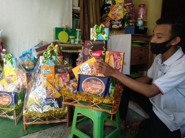 Aldi Christian, pemuda asal Kedungkandang Kota Malang saat menghias pesanan parcel usahanya. (Foto: Istimewa).