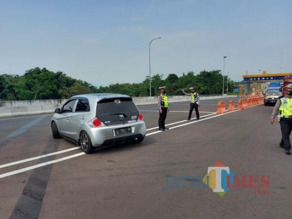 Petugas Pos Pengamanan Exit Tol Madyopuro Kota Malang saat mengarahkan kendaraan untuk berputar balik. (Foto: Tubagus Achmad/MalangTIMES)