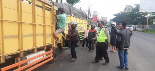 Petugas kepolisian dan masyarakat saat membantu mengevakuasi pengemudi dan kernet truk yang mengalami kecelakaan lalu lintas, Jumat (7/5/2021). (Foto: Unit Laka Lantas Polresta Malang Kota)