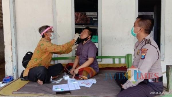 Petugas kepolisian dari Polsek Pegantenan saat mendampingi petugas medis melakukan tes swab kepada pekerja migran yang baru tiba di Pamekasan (Foto: Ist/Jatimtimes.com)