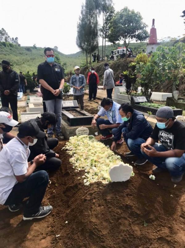 Almarhum Bambang Priana usai dimakamkan, Staf Ahli Holding Jatim Park Group Rio Imam Sendjojo (berdiri) mendoakan di TPU Dusun Junggo, Desa Tulungrejo, Kecamatan Bumiaji, Sabtu (8/5/2021). (Foto: istimewa)
