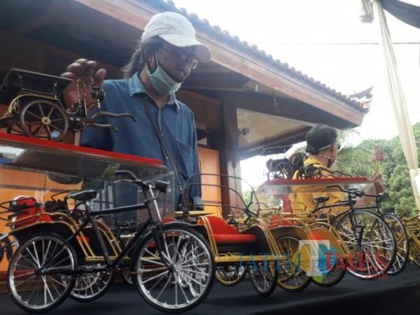 Candiono Halim bersama miniatur hasil kreasinya yang memanfaatkan limbah kabel. (Foto: Tubagus Achmad/ MalangTIMES)