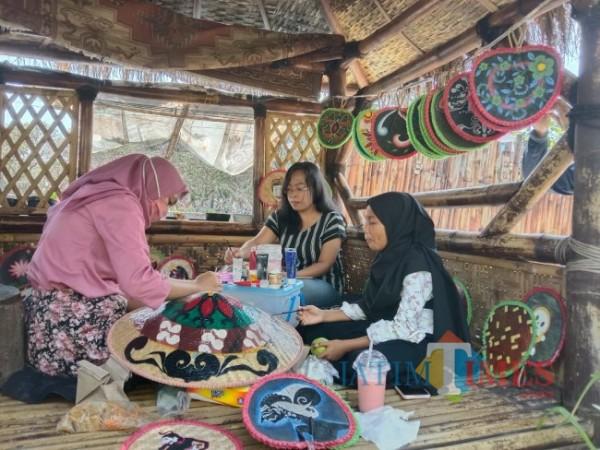 Tampak Iwut Andika bersama ibu rumah tangga lainnya saat melukis pernak-pernik yang berasal dari anyaman bambu. (Foto: Tubagus Achmad/ MalangTIMES)