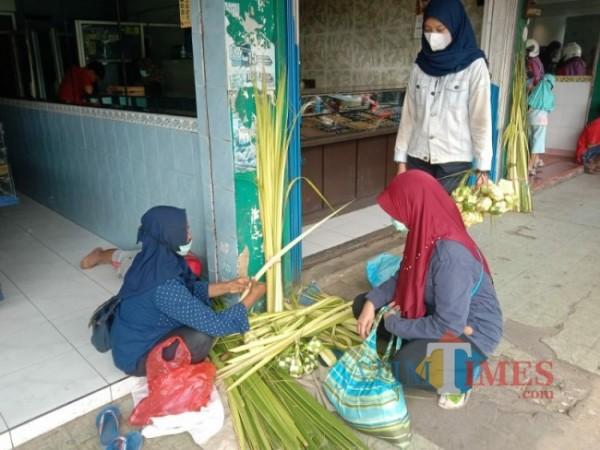 Trianah (35) pedagang anyaman ketupat yang sedang melayani pembeli di Pasar Besar Kota Batu (foto: Mariano Gale/Jatim Times)