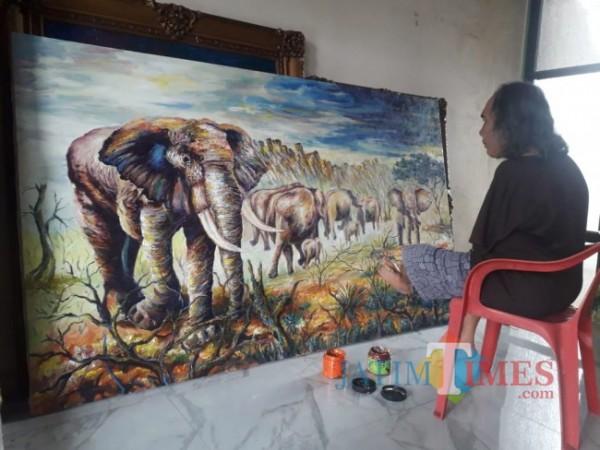 Tampak Sadikin Pard sedang melukis kawanan gajah dengan menggunakan kakinya. (Foto: Tubagus Achmad/MalangTIMES)