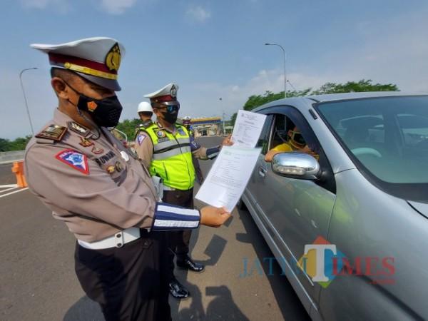 Petugas kepolisian di Pos Pengamanan Exit Tol Madyopuro Kota Malang saat memeriksa kelengkapan berkas dari salah satu pengendara. (Foto: Tubagus Achmad/MalangTIMES)