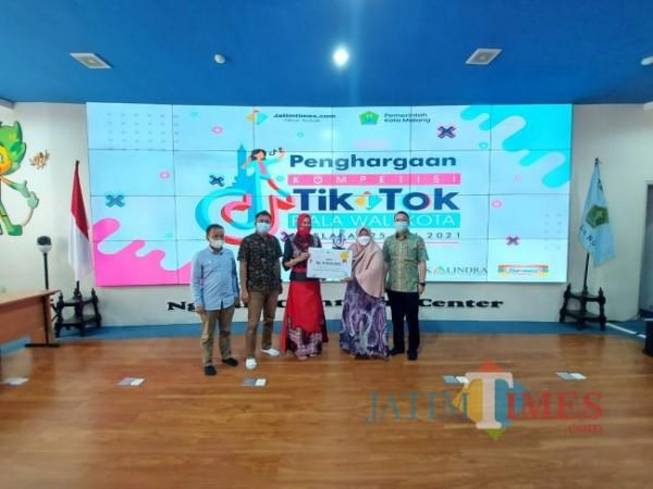 Ketua TP PKK Kota Malang Widayati Sutiaji (paling tengah) saat menyerahkan penghargaan terhadap juara 1 Kompetisi TikTok Piala Wali Kota Malang 2021 di NCC Balai Kota Malang, Selasa (25/5/2021). (Tubagus Achmad/MalangTIMES)