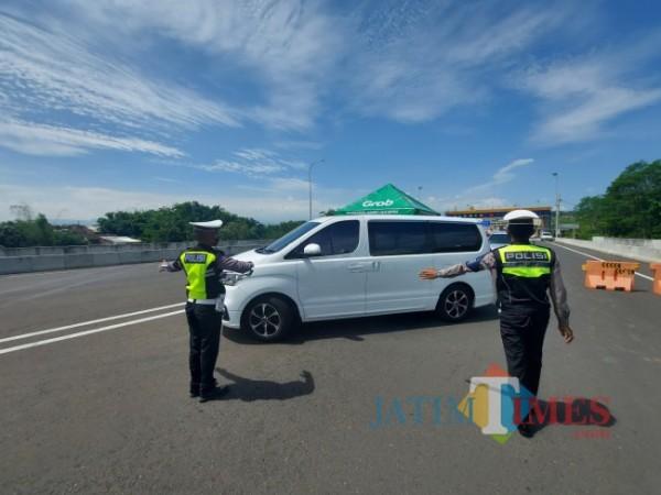 Petugas kepolisian saat mengarahkan kendaraan putar balik di pos pengamanan exit tol Madyopuro, Kota Malang. (Foto: Tubagus Achmad/MalangTIMES)