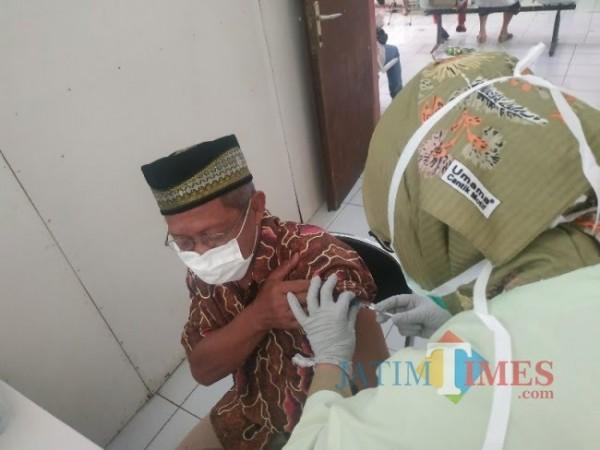 Lansia saat disuntikkan vaksin oleh tenaga kesehatan di Puskesmas Batu beberapa saat lalu. (Foto: JatimTIMES)
