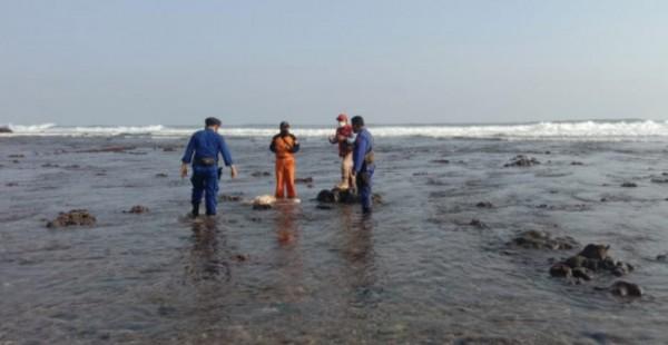 Petugas gabungan saat melihat korban Fikri yang tersangkut di bebatuan bibir Pantai Nggandol (foto: Satpolair Polres Malang for MalangTIMES)