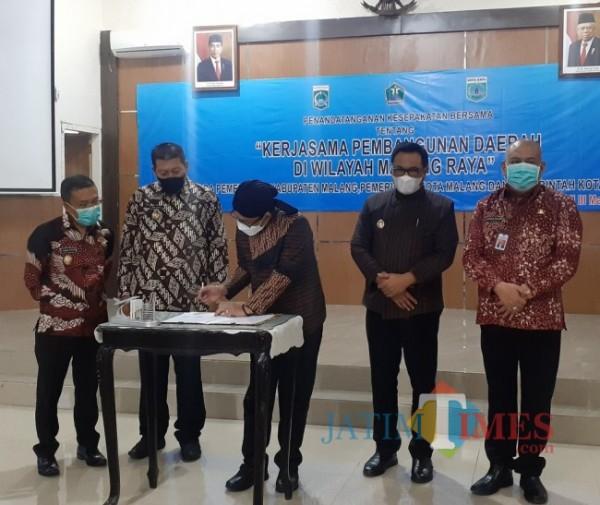 Wali Kota Malang Sutiaji (paling tengah memakai blangkon) saat menandatangani kesepakatan bersama 3 daerah Malang Raya, di Kantor Bakorwil III Malang, Kamis (27/5/2021). (Arifina Cahyanti Firdausi/MalangTIMES).